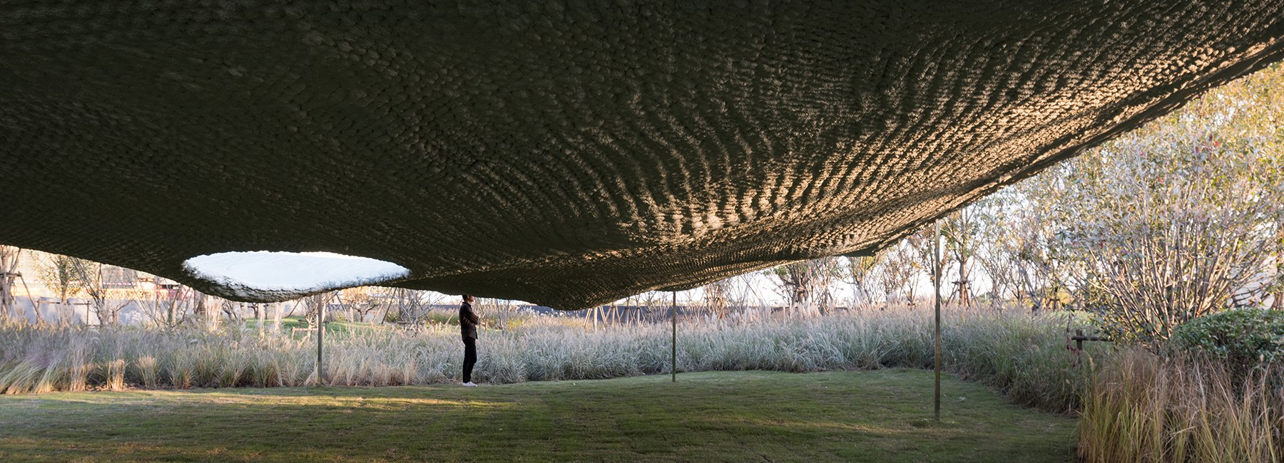 the undulating 'soft matter' pavilion takes inspiration from its site's unnatural geology
